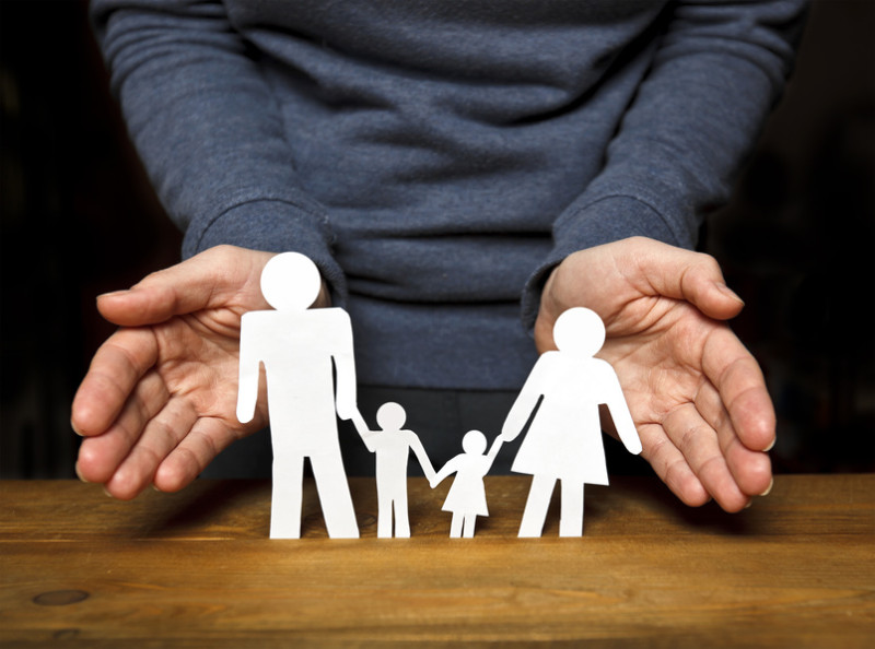 Paper family on wooden table and woman hands protect them